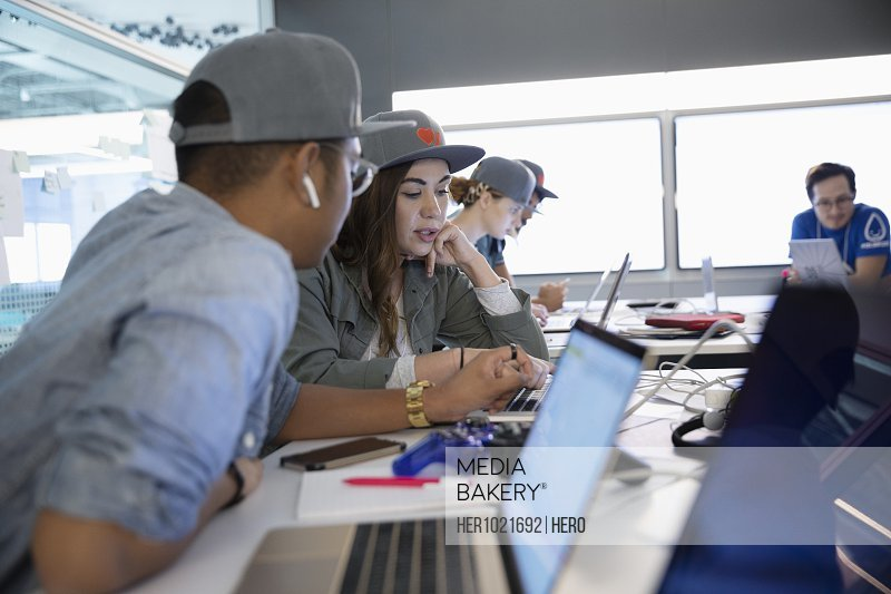 Millennial hackers using laptops in office during hackathon