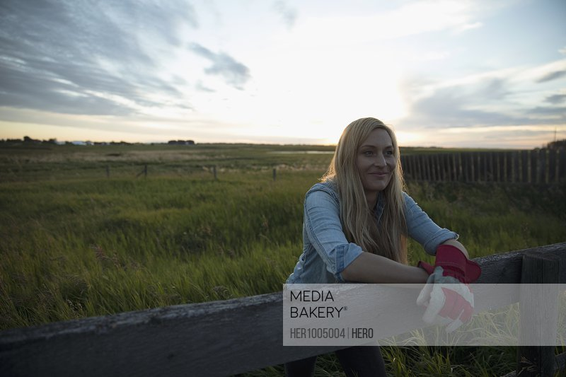 Confident young female farmer leaning on fence on farm at sunset