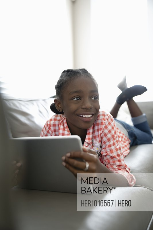 Smiling tween girl using digital tablet on living room sofa