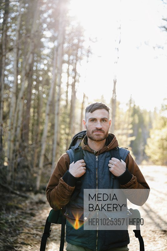 Portrait confident man with backpack hiking in woods