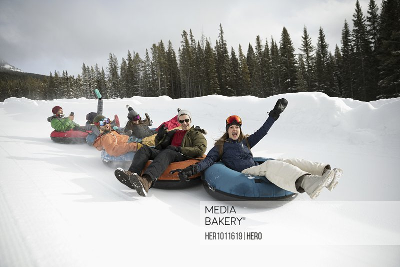 Portrait playful friends riding inner tubes in snow