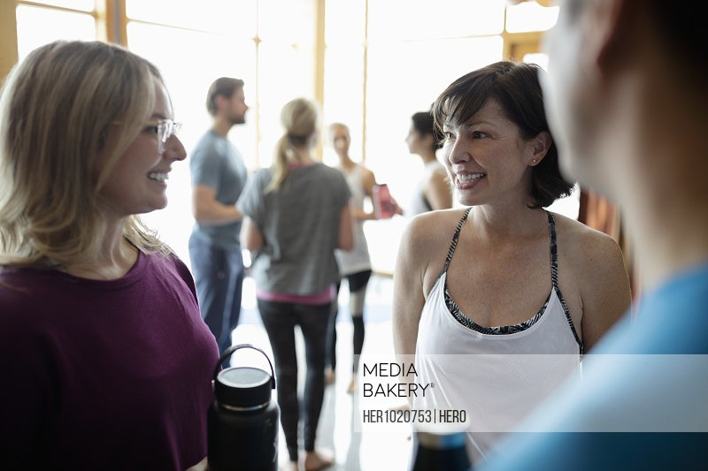 Women friends talking after yoga class in studio