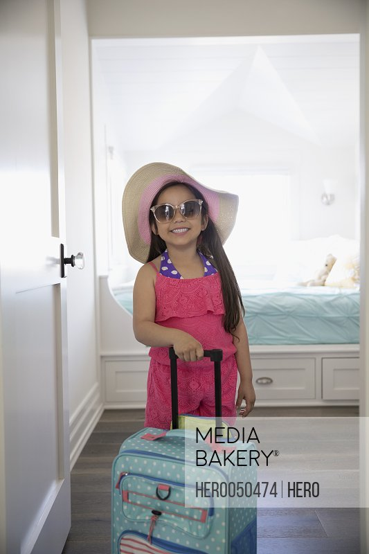 Portrait smiling Latina girl in sunglasses and straw hat with suitcase ready for vacation