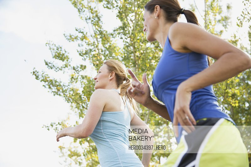 Two women running outdoors together.