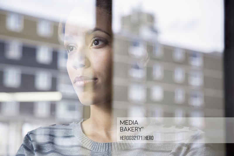 reflection in window of pretty african american businesswoman