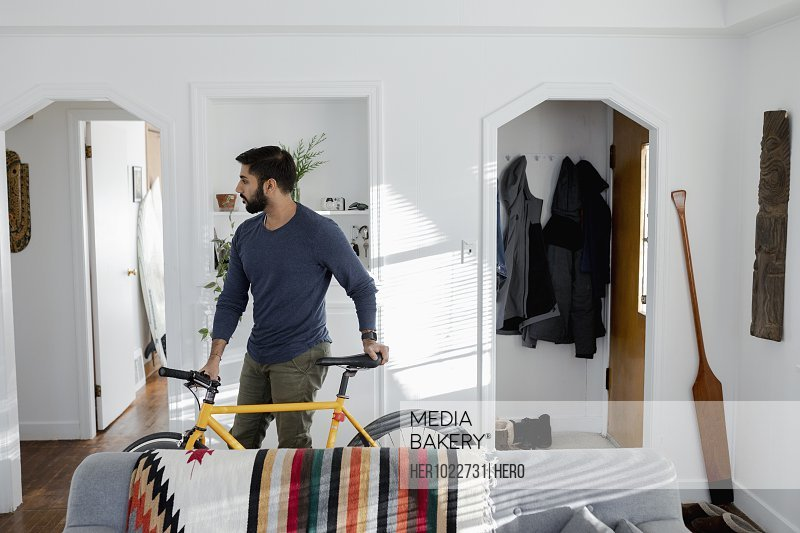 Man with bicycle in apartment