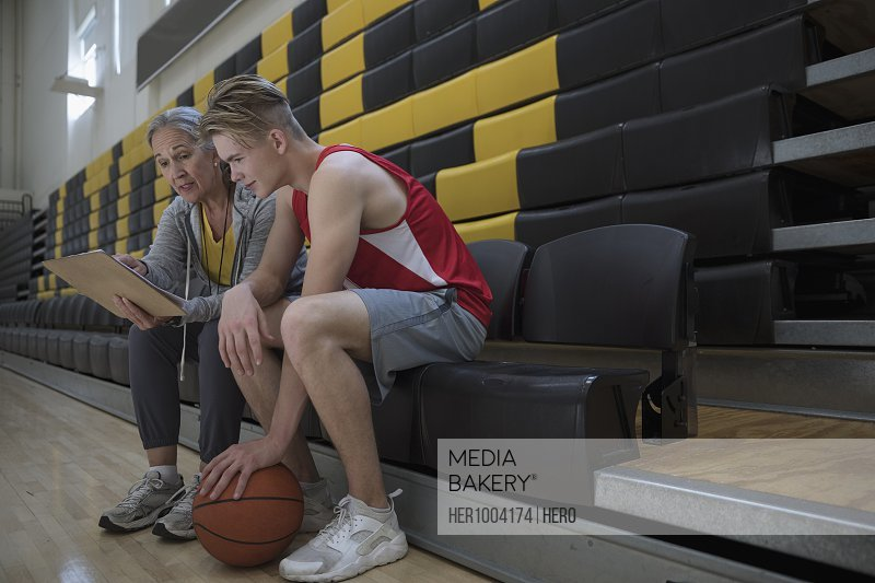 Female coach coaching male college basketball player in gymnasium