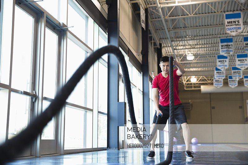 Man exercising with power ropes in fitness center