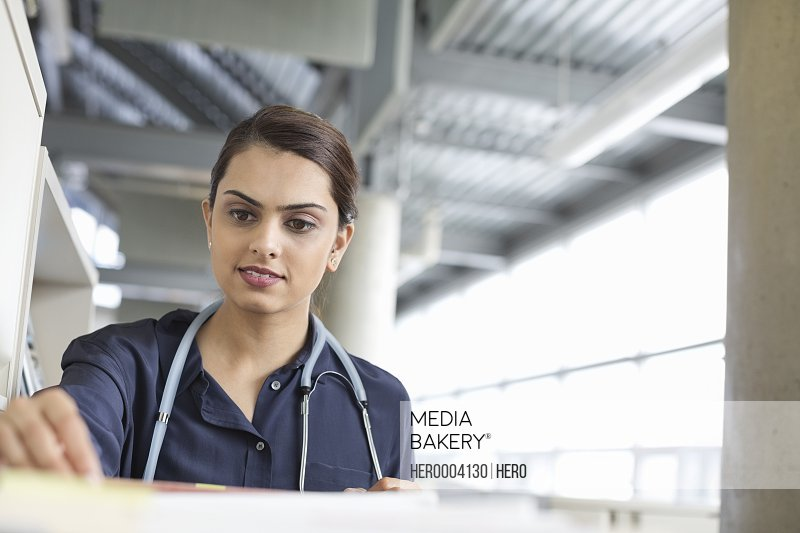 Medical professional looking through filing cabinet