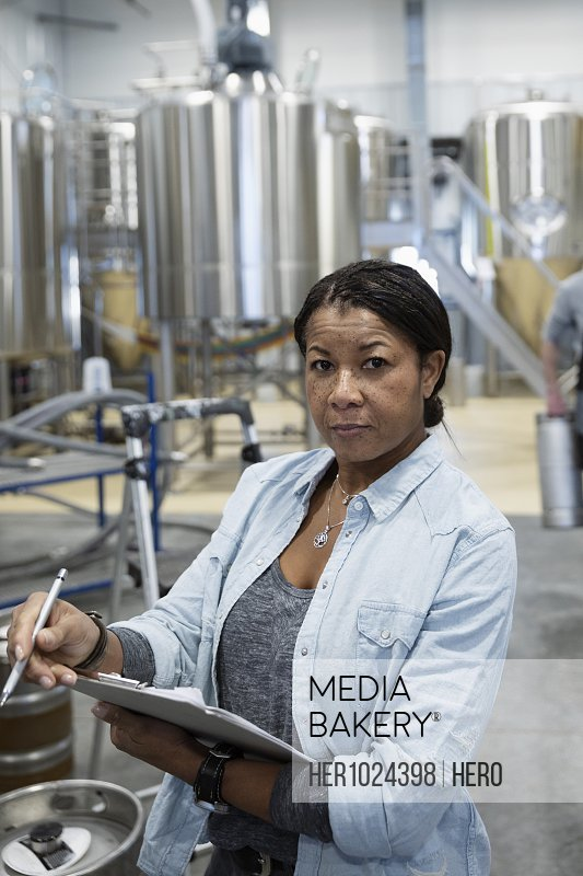 Portrait confident female brewer with clipboard working in brewhouse distillery