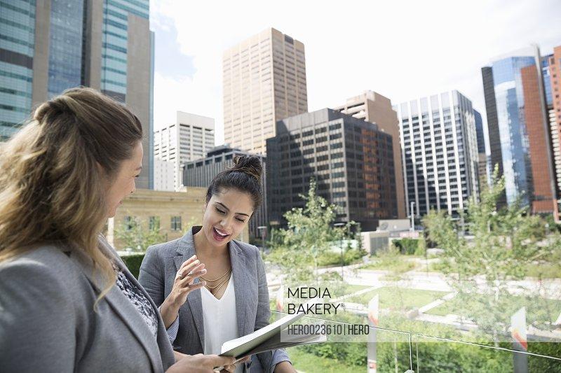 Businesswomen discussing paperwork in city