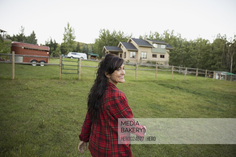 Smiling woman walking in rural pasture