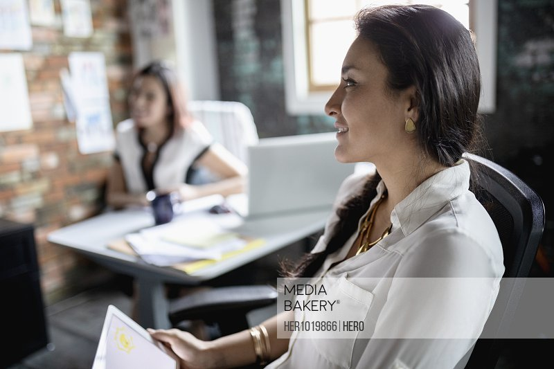 Smiling creative businesswoman with digital tablet listening in office