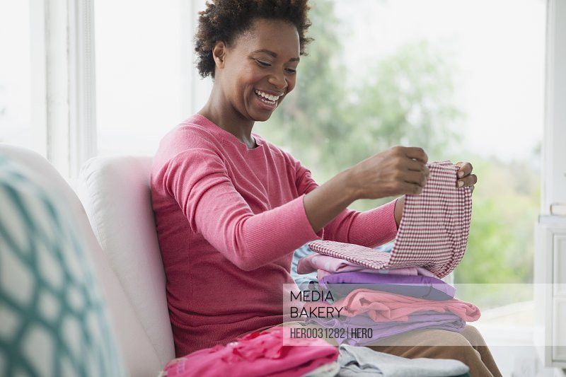 mid adult woman folding clean laundry
