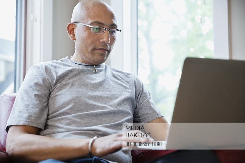 Mature man browsing on laptop at home