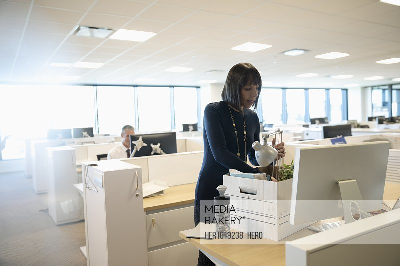 Businesswoman unpacking belongings on first day in new office