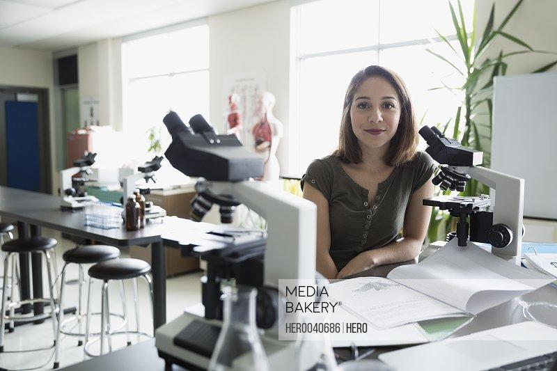 Portrait confident college student at microscope in science laboratory