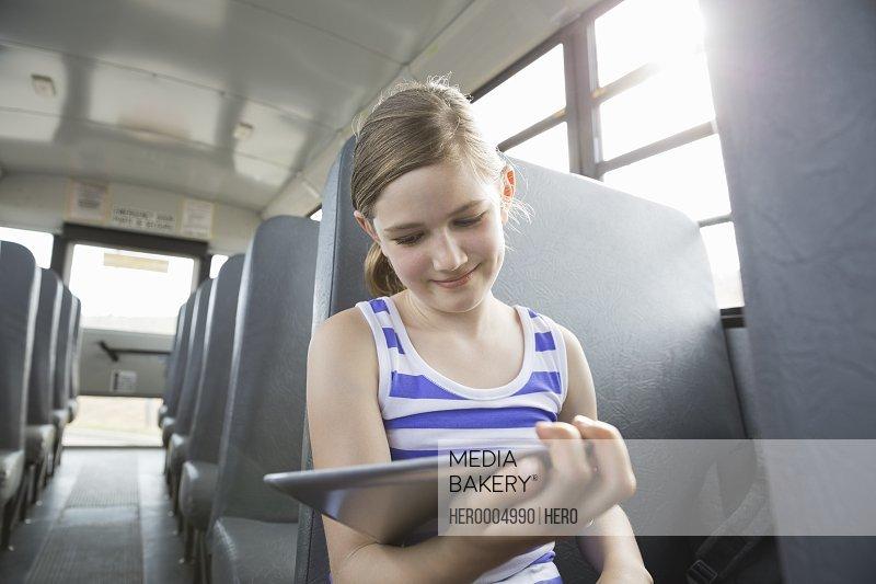 Smiling girl looking at digital tablet inside school bus