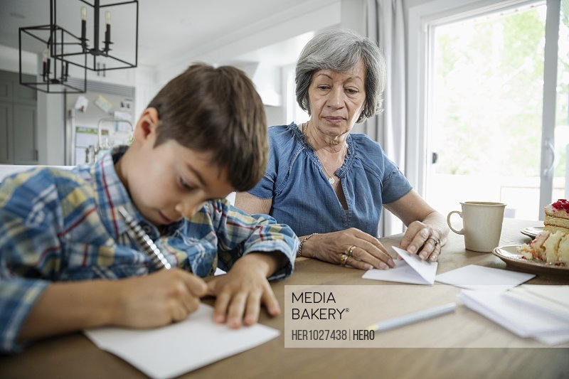 Grandmother and grandson writing letters at dining table