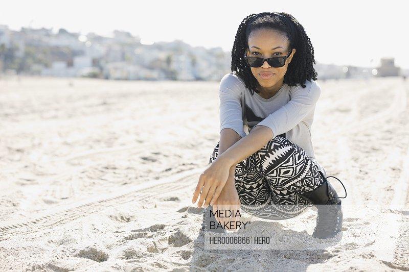 Confident woman crouching on sandy beach
