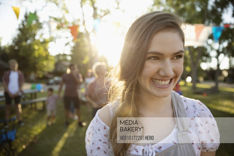 Portrait smiling confident teenage girl at summer neighborhood block party in park