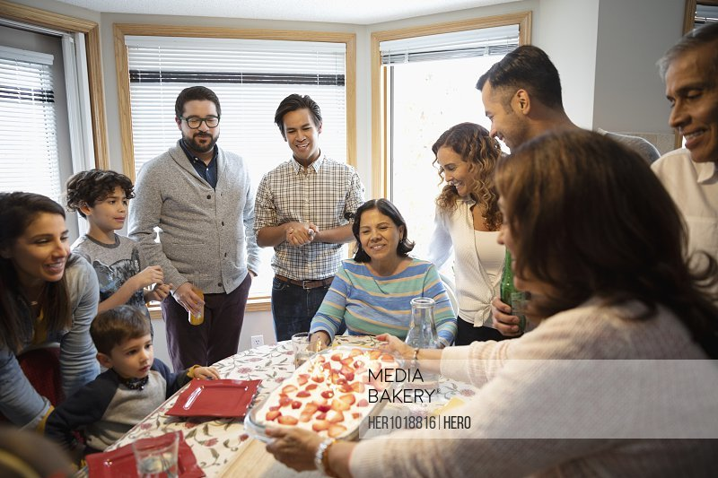 Latinx grandmother serving strawberry cake to family