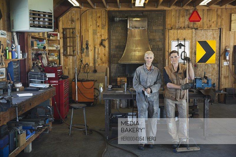 Portrait of metal smiths standing in workshop