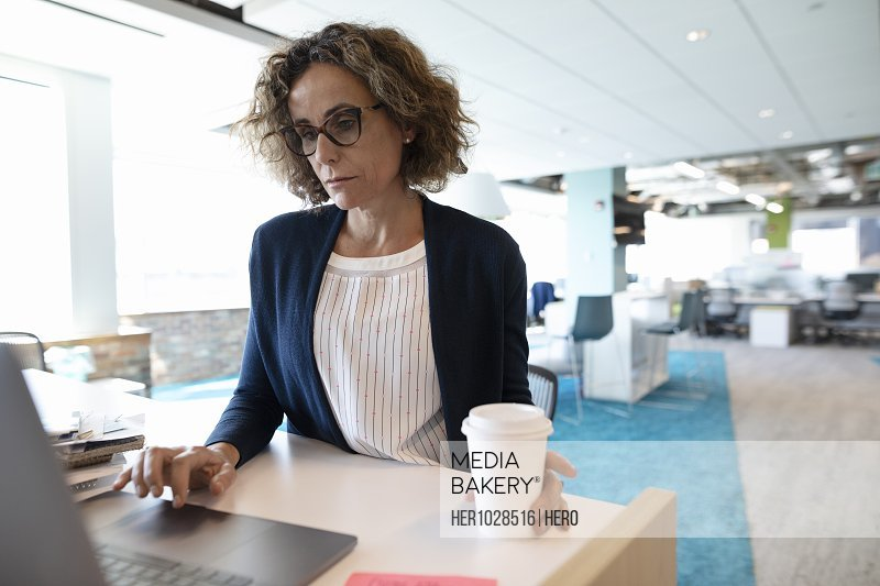 Mature businesswoman using laptop with coffee