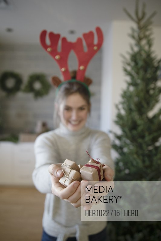 Portrait teenage girl in reindeer antlers holding small Christmas gifts