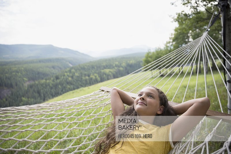 Serene girl laying in rural hammock looking up with hands behind head