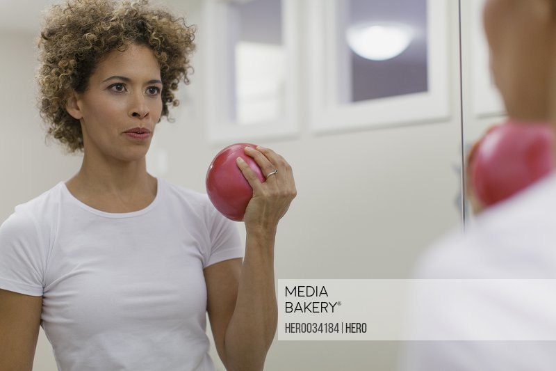 Woman using medicine ball in workout.