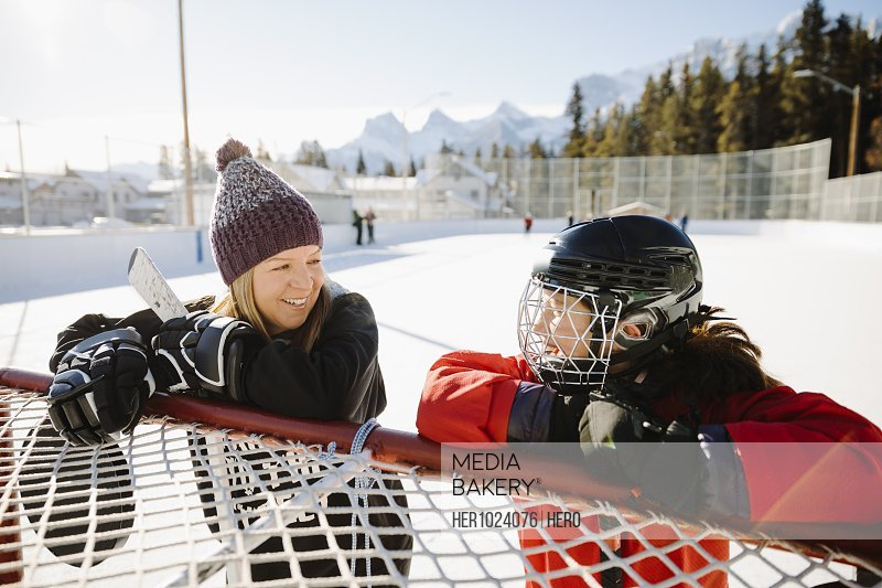 Happy mother and daughter playing outdoor ice hockey, taking a break at goal