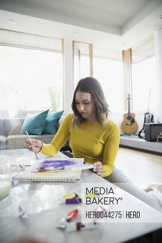Young woman painting with watercolors in living room