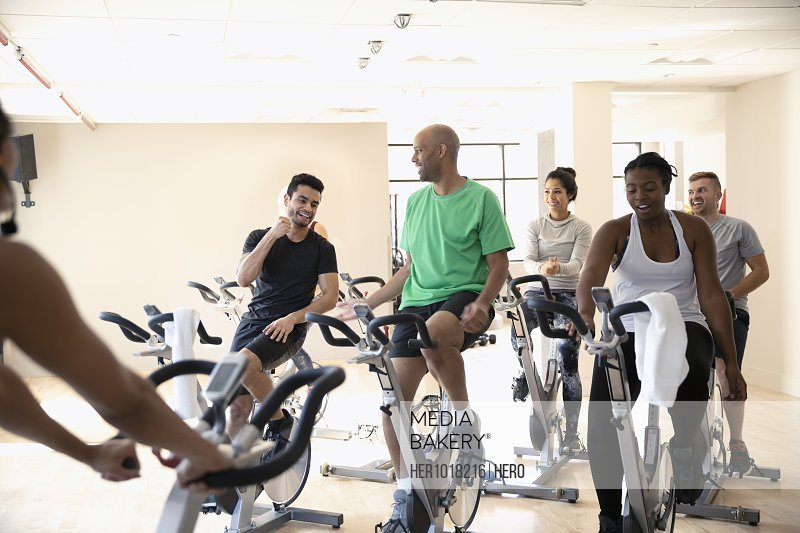 Men high-fiving on exercise bikes in spin class in gym