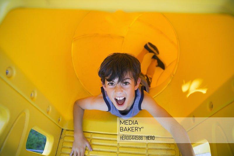 Portrait playful boy inside yellow playground slide