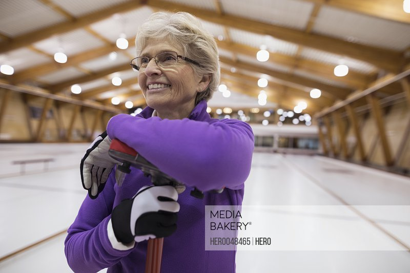 Smiling senior woman curling