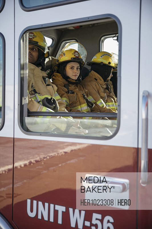 Female firefighter riding in fire engine