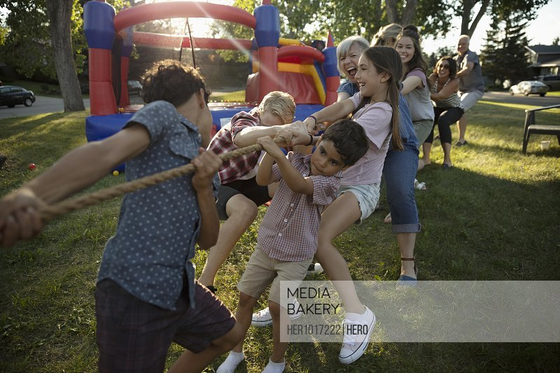 Kids and neighbors playing tug-of-war at summer neighborhood block party in park