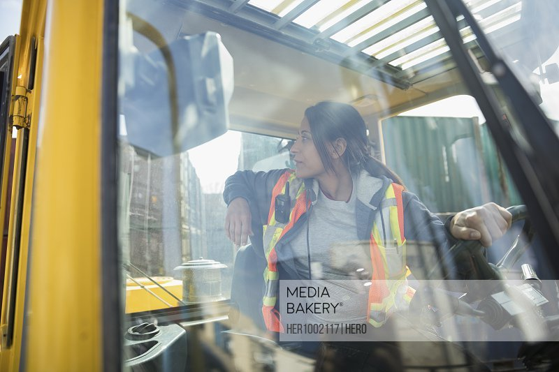 Female forklift driver inside forklift in industrial container yard