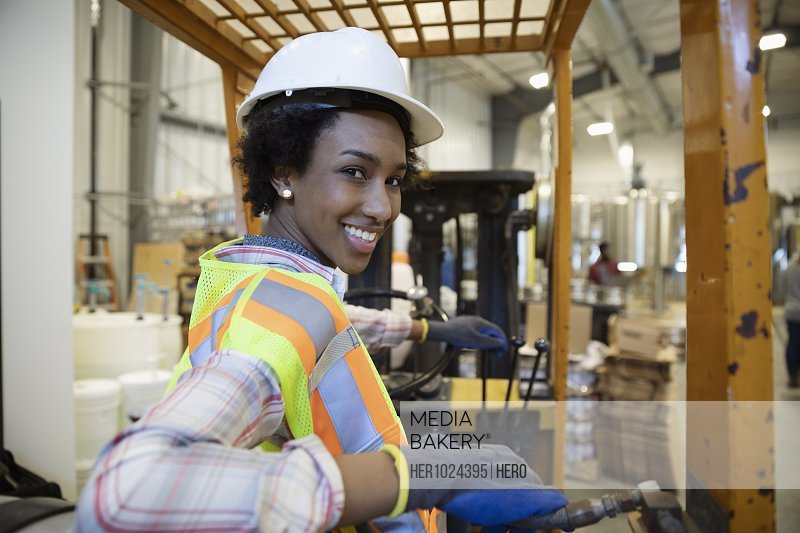 Portrait confident female brewer operating forklift in distillery warehouse