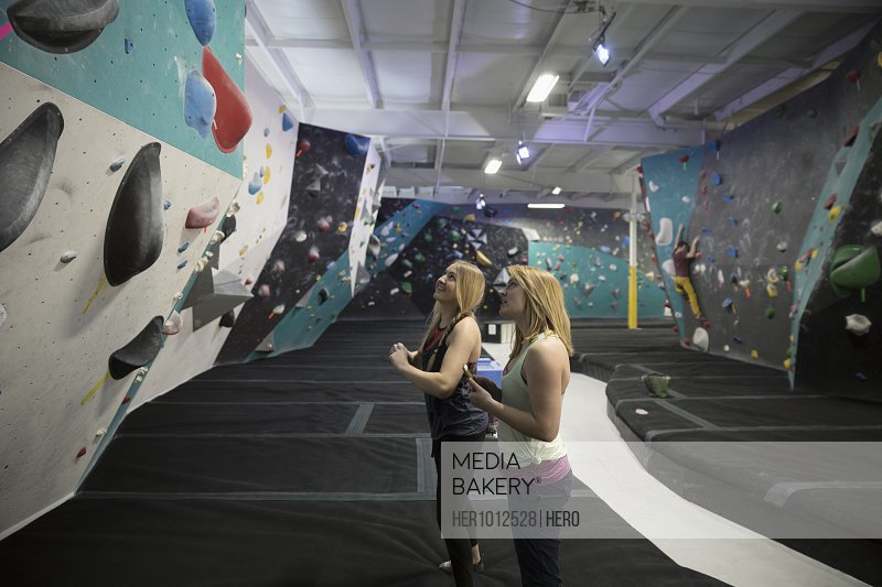 Female rock climbers looking up at climbing wall in climbing gym