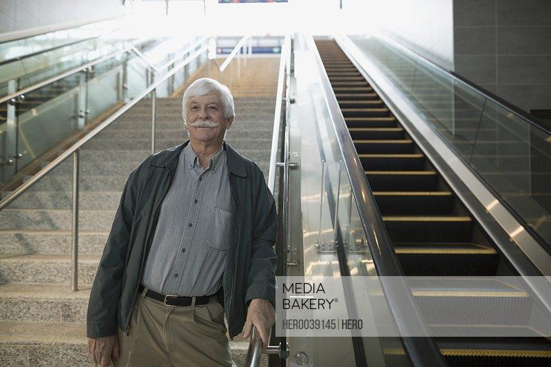 Portrait smiling senior man mustache train station stairs