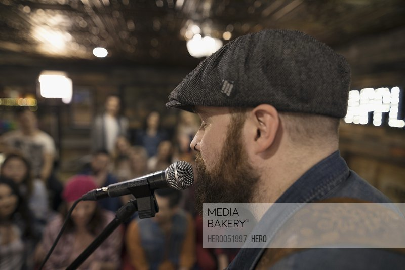 Close up male singer singing at microphone with audience in background