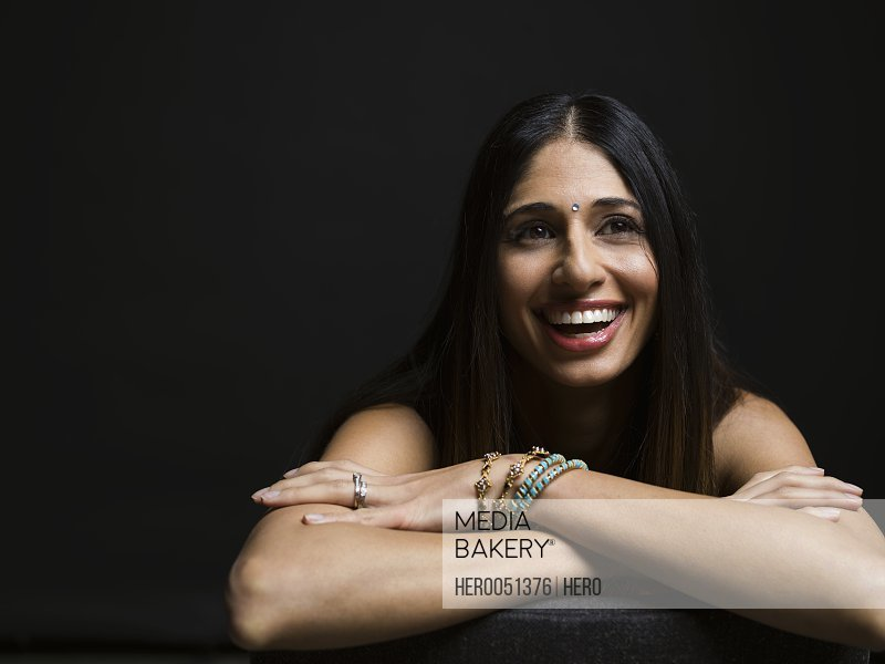 Portrait laughing Indian woman with bindi against black background