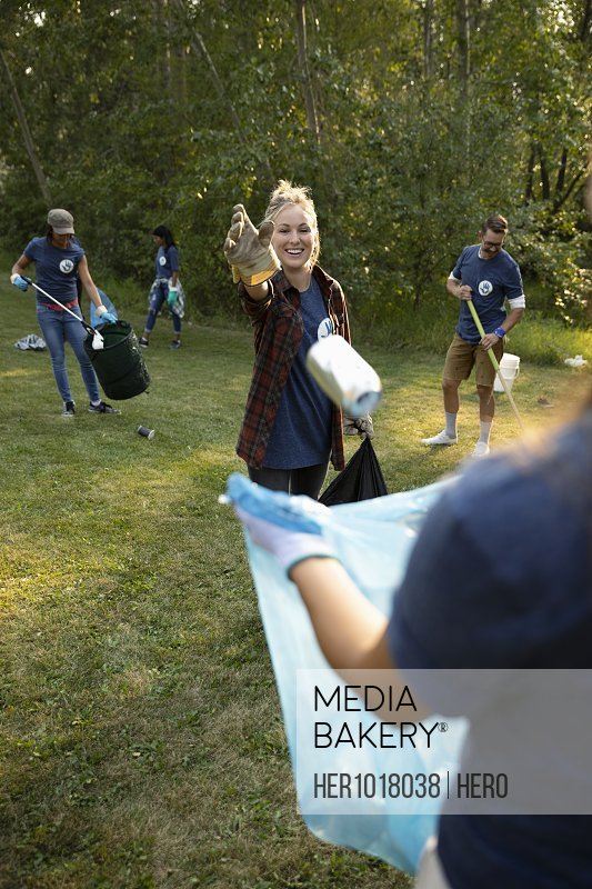 Young woman volunteering, cleaning up garbage in park