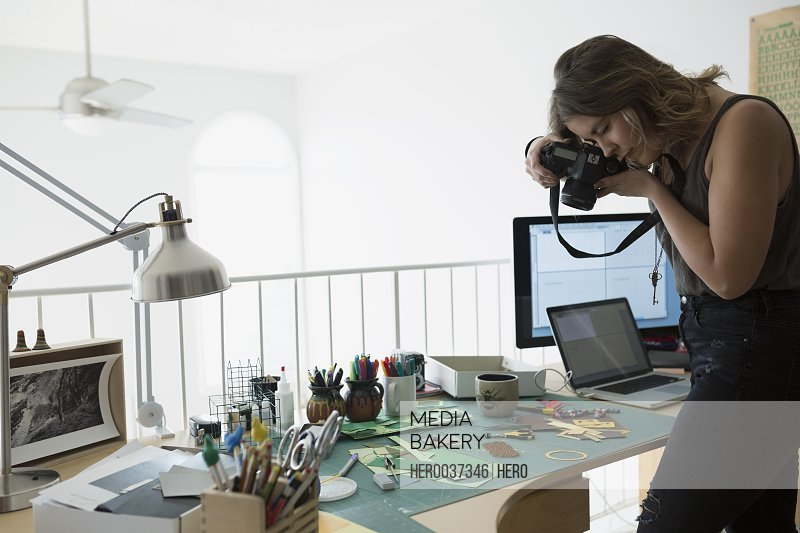 Craftswoman photographing pieces on desk in home office