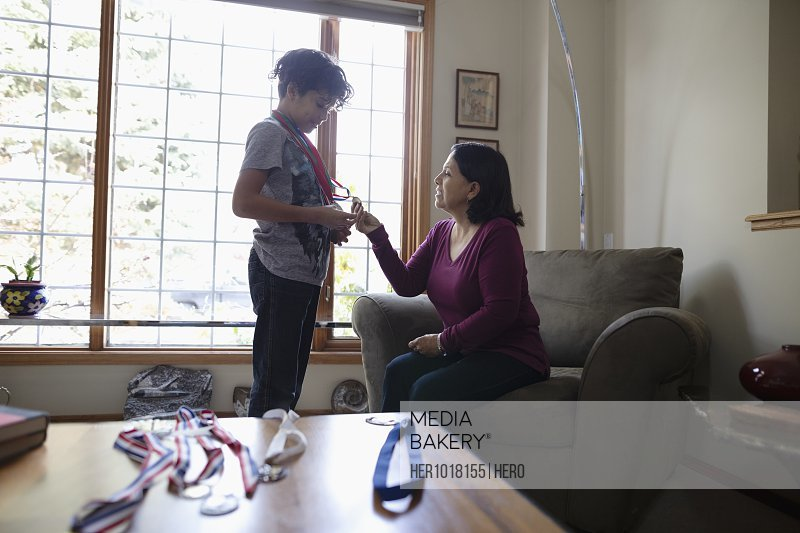 Latinx grandson showing sports medals to grandmother