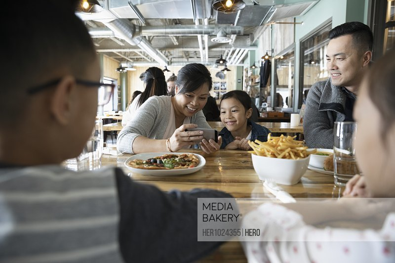 Family with smart phone dining at restaurant table