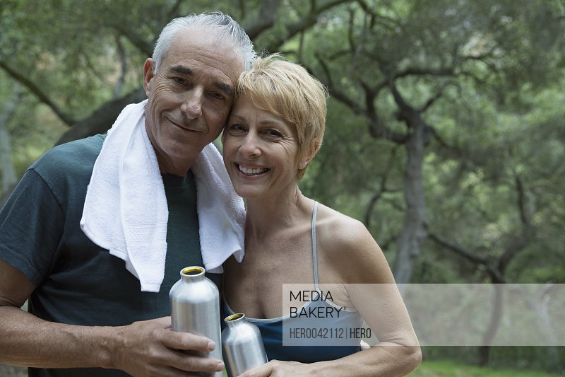 Portrait smiling couple with water bottles outdoors