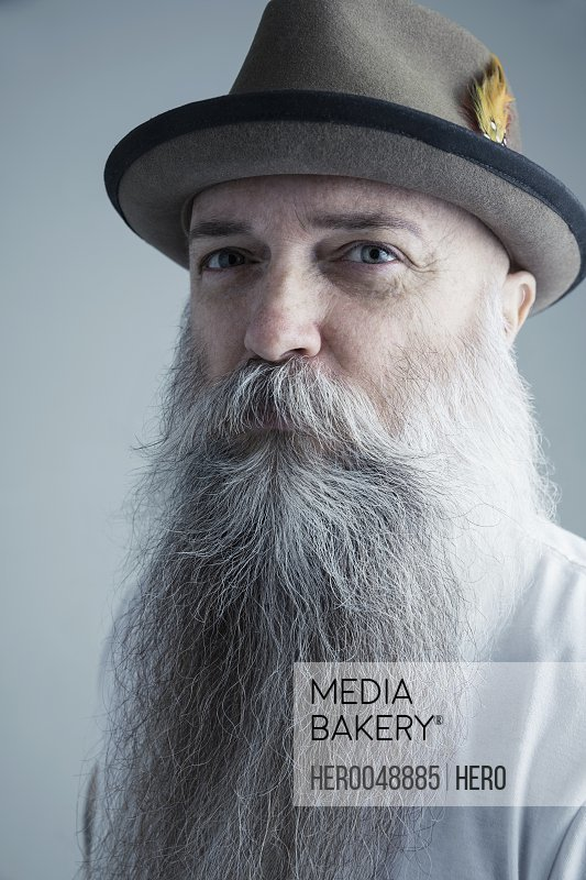 Portrait confident Caucasian male hipster with long gray beard wearing fedora